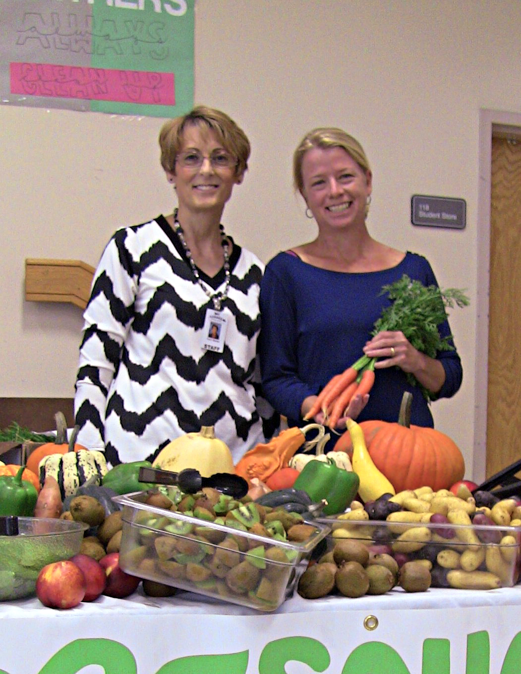 Nutrition Director and Farmer stand at display table full of produce for Taste Washington Day